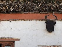 Wall of a Tibetan house with a sacred Buddhist talisman protector - the head of a black bull with large horns, large free space fo. The wall of a Tibetan house Royalty Free Stock Photography