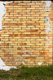 Wall with torn posters. Brick wall with torn posters - yellow and red bricks background Stock Photos