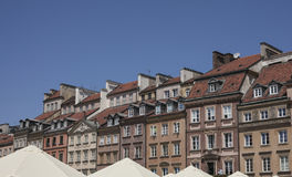 A wall of town houses. This picture shows a view of a wall of old-fashioned town houses in Warsaw, Poland. There are some tops of big umbrellas visible at the Royalty Free Stock Images