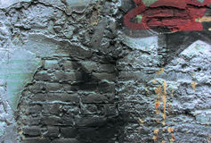 Wall with traces of graffiti. The damaged and charred fragment of graffiti on a brick wall stock photo
