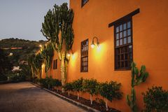 A wall of a traditional guest house with lights switched on in Canary Islands with large cactus plants on its side royalty free stock photos