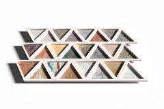 Wall with triangles of different materials in white frames Stock Images