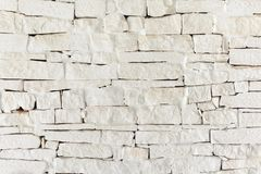 A wall of uneven bricks painted with beige paint. Blank background with texture royalty free stock photos