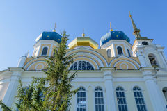 Wall and upper part of church with three blue and gold domes Royalty Free Stock Photo