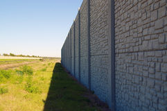 Wall with vanishing point and field. Looking down the length of a tall preformed wall beside a field of grass Royalty Free Stock Images
