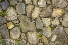 Wall of various large natural stones with small green vegetation. wall with moss. rough wall surface texture. gray, blue and white. A wall of various large royalty free stock images