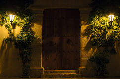 Wall with vintage massive wooden door and two lit street lamps Stock Images