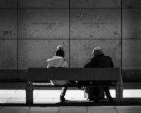 The Wall Watchers. Two women sit looking towards a wall in Manchester in full winter clothing. Black and White stock photo