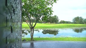 A wall waterfall in the pool with a view of the pond and a green golf course. A wall waterfall with falling water in the pool with a beautiful view of the pond stock video footage