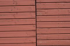 Wall of weathered, cracked, faded and split tongue and groove boards. The boards have been painted red, which has faded, and are installed with a horizontal royalty free stock images