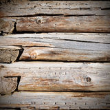 Wall from weathered old logs with cracks. Grunge background Stock Photos