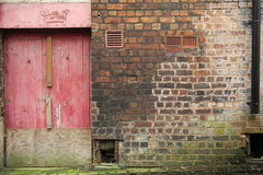 Wall with weathered red door Royalty Free Stock Photo