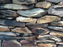 The wall which made up of rocks. Rocks background in many types and colors of rocks Royalty Free Stock Photos