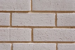 Wall of white bricks with yellow fugue. Wall of decorative white bricks with yellow fugue Stock Images