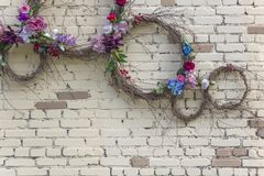 Wall of white and brown bricks with round rings of dry branches of different sizes and colorful flowers. rough surface texture. A wall of white and brown bricks royalty free stock image