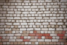 Wall of white and red bricks with uneven old masonry stock photography