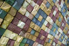 Wall of wild stone in different colors lined with a pattern stock image