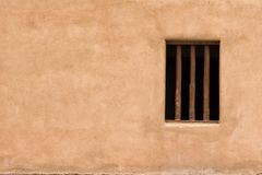 Wall with a window. Window in adobe wall Stock Image