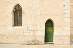 Wall with a window and a door. Old stone wall with a window and a green door Royalty Free Stock Photo