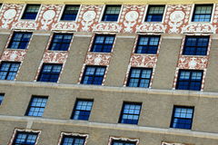 Wall of windows with intricate carvings around the upper rows Royalty Free Stock Photos