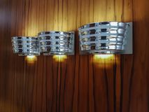 A wall of wood panels and three creative lamps in a nickel housing. royalty free stock photography
