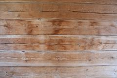 Wall of a wooden building close. Texture of a wooden wall of tightly knit boards Stock Photos