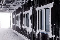 The wall of the wooden house in the ski resort, white window frames covered snow and hoarfrost. Side view royalty free stock image
