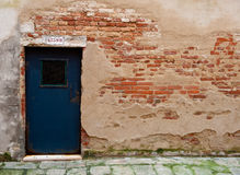 Wall wth exposed brick, door, venice, italy. Exterior wall with missing plaster exposing brick wall, blue door Stock Images