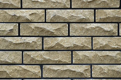 Wall of yellow bricks. With black cement layers Stock Photos