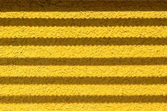 Wall of yellow color with fittings shadow strips Stock Photos