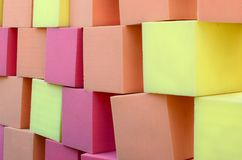 Wall of paralon soft cubes in dry pool, trampoline in the childrens center. Wall of yellow and red paralon soft cubes in dry pool, trampoline in the childrens royalty free stock images
