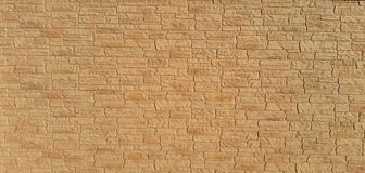 Wall with a yellowish stone texture royalty free stock image