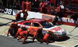 Wallace's Pit Crew. Kenny Wallace's pit crew races to complete their pit stop as fast as possible as NASCAR officials watch closely during 2007 Crown Royal Royalty Free Stock Photos
