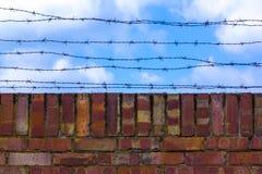 Wallagainst del mattone e del filo spinato il cielo blu Il cielo blu ? coperto di filo spinato Prigione e cielo nuvoloso blu fotografia stock libera da diritti
