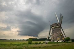 Wallcloud of a supercell thunderstorm near a windmill in The Netherlands. Classic dutch windmill against a dramatic storm sky. A rotating thunderstorm with large royalty free stock photo
