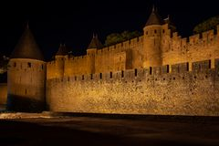 Walled city of Carcasone during the start of the night. View of the outer wall xon its defensive towers. stock image