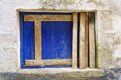 Walled fönster med ett blått bräde och ett omålat horisontal och en ver Arkivbilder