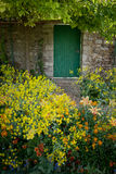 Walled garden gate. A path almost hidden by flowers leads to a doorway in an old stone wall Royalty Free Stock Photography