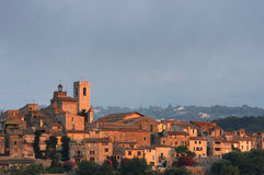 Walled hilltop village lit by sun's first rays. Walled hilltop village Saint Paul de Vence, in the foothills of the Alps just north of the Cote d'Azur, lit by Royalty Free Stock Images