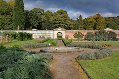 Walled kitchen garden with a pathway and a circular fountain royalty free stock photo