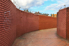 Walled Path With Blue Sky. Curving walled path with graffitied red brick walls topped with barbed wire stock image