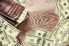 Wallet and banknotes of dollars. Photo wallet and banknotes of dollars on wooden background Royalty Free Stock Photos
