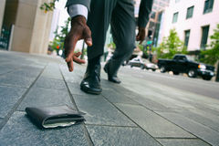 Wallet:. Businessman loses wallet outside on sidewalk Royalty Free Stock Photos
