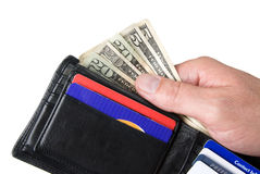Wallet and cash. Dishing out cash from a leather wallet to pay bills Royalty Free Stock Photography