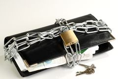 Wallet in chains. Security concept black leather wallet in chains on a white background Royalty Free Stock Photo