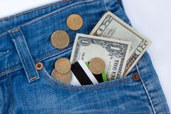 Wallet, credit cards and ready money are lying in side pocket of blue jeans stock photography