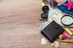 Wallet, dollar, passports, compass, seashell  on wood background Royalty Free Stock Photography