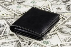 Wallet on Dollars Background. Leather wallet on a dollars background Stock Photo