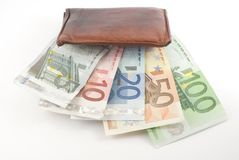 Wallet Eating Money. Wallet full of euro banknotes. Isolated on white Royalty Free Stock Photo