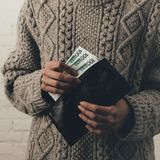 Wallet with euro banknotes. Cropped view of woman in sweater holding wallet with euro banknotes Royalty Free Stock Images